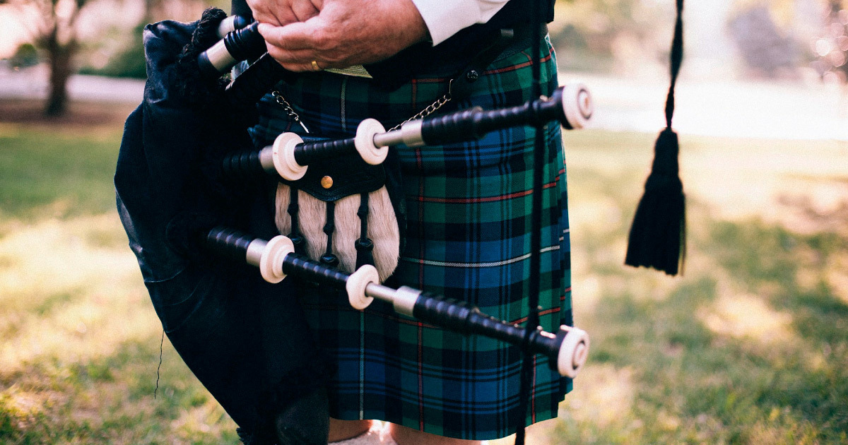 Bagpiper in kilt holding bagpipes. Image Source: https://pixabay.com/photos/bagpipe-scot-uilleann-pipes-349717/