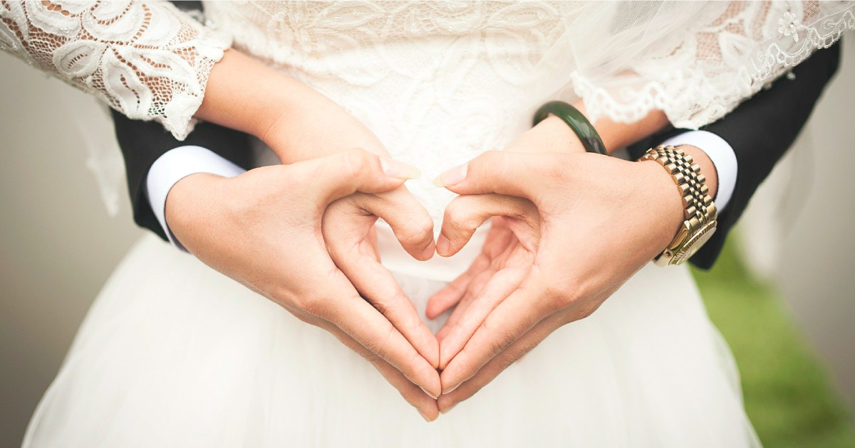 Photograph of two people holding hands in a heart shape. Image Source: https://pixabay.com/photos/heart-wedding-marriage-hands-529607/