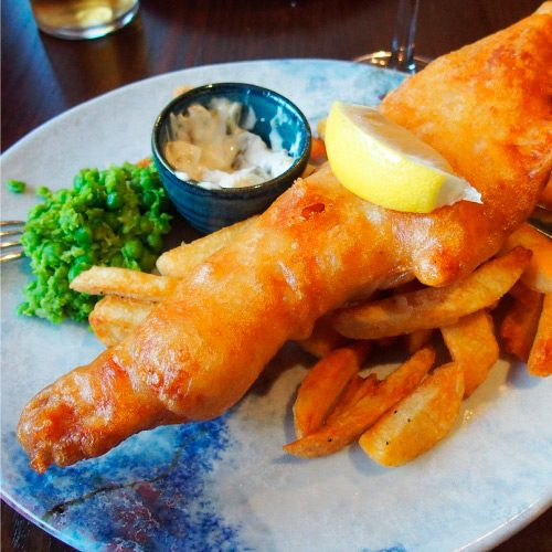 Photograph of a Fish in batter with a slice of lemon on top of some chips, with mushy peas and tartare sauce, on a plate. Image Source: https://pixabay.com/photos/fish-and-chips-scotland-2753360/